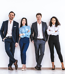 4 employees standing against a white wall